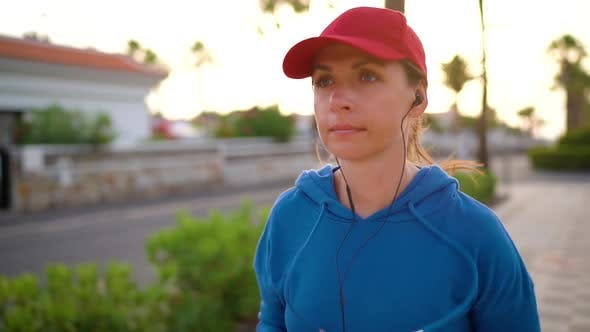 Thumbnail for Woman with Headphones Runs Down the Street Along the Palm Avenue at Sunset. Healthy Active Lifestyle