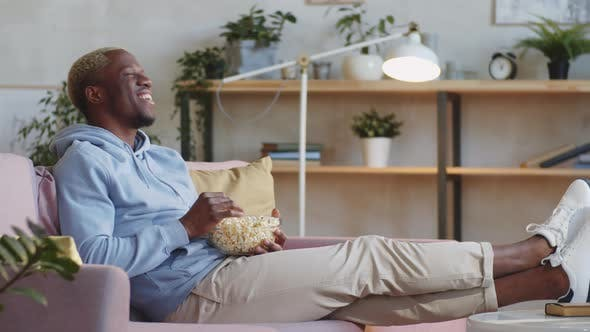 Schwarzer Mann lacht und schaut Film zu Hause