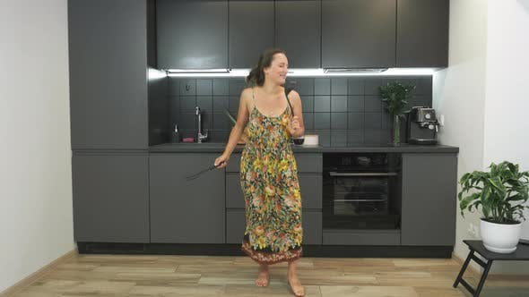 Thumbnail for Cute joyful caucasian young woman in home wear is having fun and dancing with kitchenware