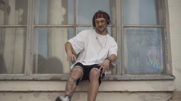 Thumbnail for Confident Male Break Dancer with Tattoos and Dreadlocks Sitting on Urban Windowsill in Headphones