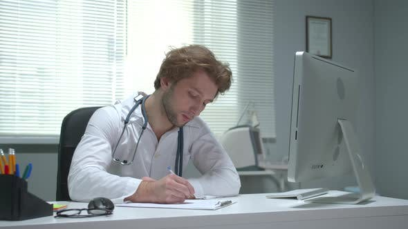Doctor Sit at a Table in Cabinet of Hospital and Write