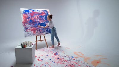 Female Artist Draws with Her Hands on a Large Canvas in a White Room a Talented Artist Draws a Color