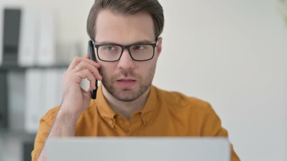Thumbnail for Close Up of Young Man with Laptop Talking on Smartphone