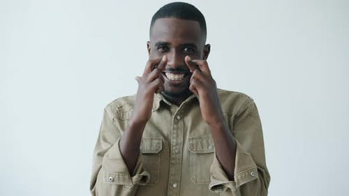 Portrait of Joyful African American Man Crossing Fingers Makign Wish on White Background