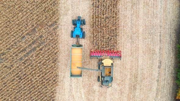 Thumbnail for Aerial Shot of Combine Loading Off Corn Grains Into Tractor Trailer. Flying Over Agricultural