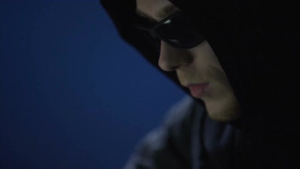 Cover Image for Closeup of Man in Sunglasses Committing Crime, Illegally Using Company Computer