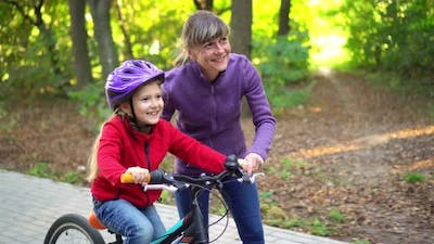Mother teaching daughter to ride bike at urban park. Child girl learning biking with the mom  help