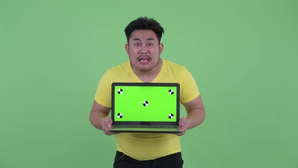 Thumbnail for Happy Young Overweight Asian Man Showing Laptop and Looking Surprised