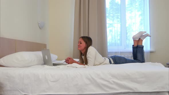 Thumbnail for Happy Woman Lying on the Hotel Bed Having Video Call Via Laptop