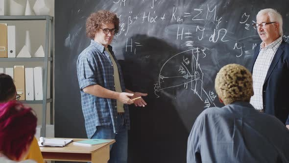 Thumbnail for Male High School Student Answering Questions of Professor beside Chalkboard