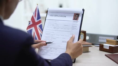 Embassy Specialist Denying Visa Application Sitting Office, British Flag Table