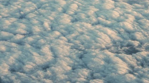 Airplane Flight Of Sunlit Clouds Covering Landscape