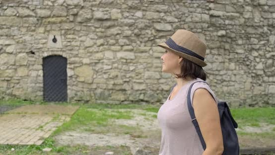 Thumbnail for Woman Tourist in Hat with Backpack Walking in the Park Near Ancient Medieval Castle