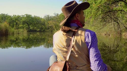 Cowboy in a Canoe Floats on the River