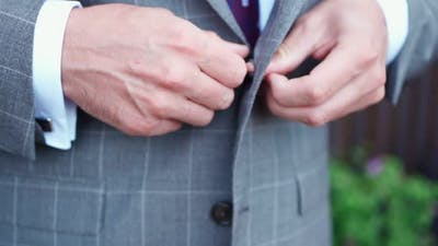Man Fastens Button on His Jacket Before Wedding Ceremony