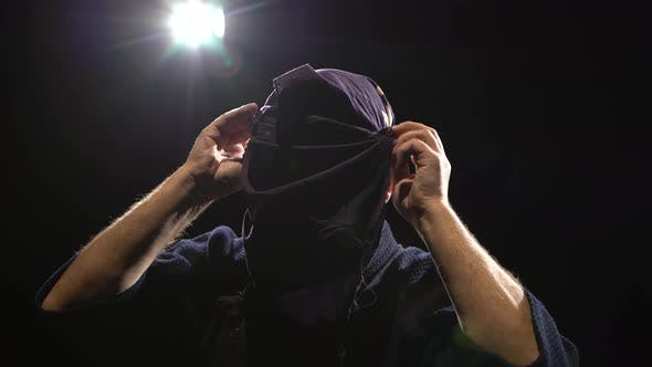 Close-up of Kendo Warrior Is Putting on Helmet at Background Spotlights. Dolly Shot