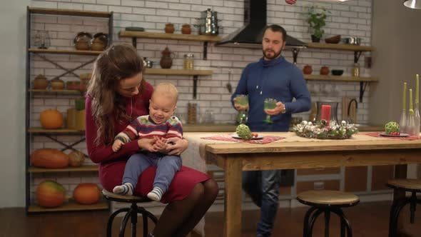 Cover Image for Young Pretty Woman Sitting at the Table in the Kitchen with Baby on Her Pals While Handsome Bearded