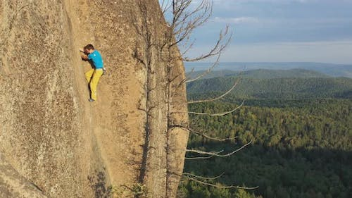 Aerial Shot of a Young Man Climbing a Rock Crack To the Top of a Mountain Without Insurance
