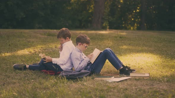 Schoolboys Read Books Sitting on Green Lawn After Lessons