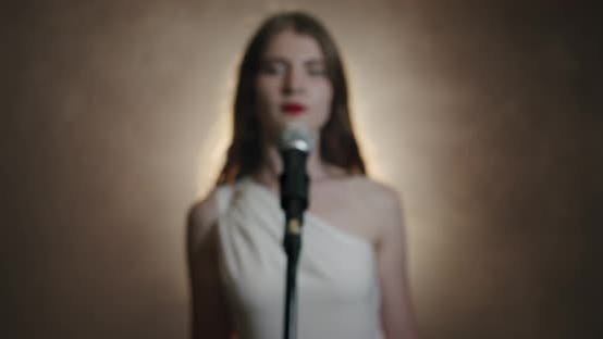 Thumbnail for The Girl Singer Approaches the Microphone and Begins To Sing, the Scene in Smoke