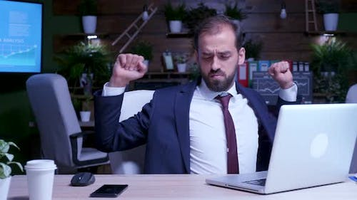 Businessman Tries to Relax Late at Night in the Office