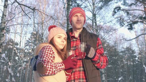 Couple of Smiling Young People in Winter in the Park at Sunset Drinking Hot Mulled Wine