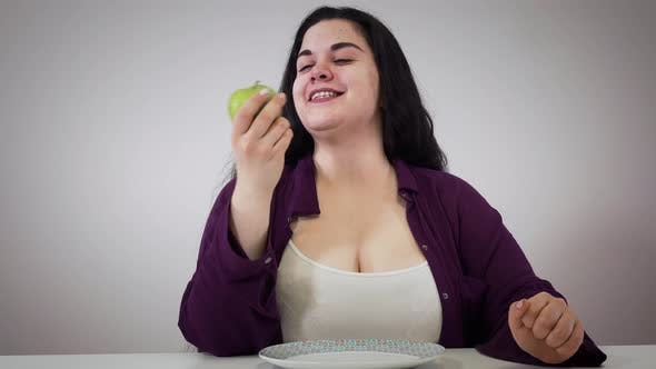 Thumbnail for Portrait of Cheerful Obese Caucasian Woman Sitting at the Table and Eating Apple. Smiling Brunette