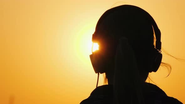 Thumbnail for Rear View of a Child with Headphones Listening To Music and Admiring the Sunset and a Big Orange Sky