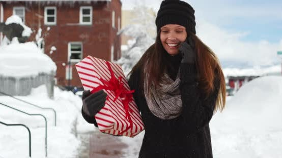 Thumbnail for Woman talking on cellphone while holding Christmas gift on snowy street downtown