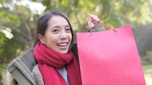 Happy woman holding paper bag at park