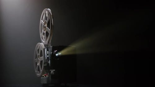 Projector Illuminated By Lights Broadcasts a Movies. Dark Studio