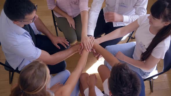 Thumbnail for Group Therapy, Women and Men Stack Hands As Symbol for Support Sitting in Circle on Chairs