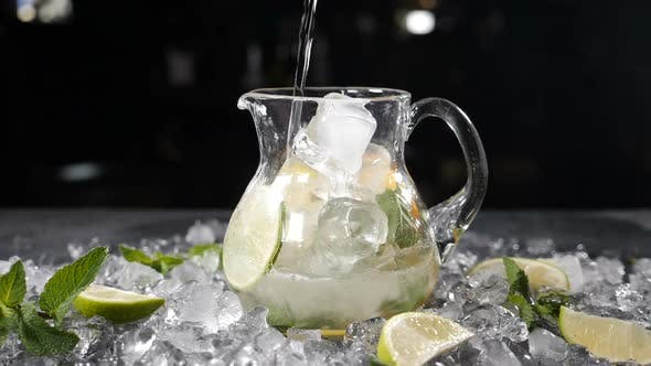 Sparkling Soda Water Being Poured Into Glass Jar Filled with Sliced Lime Mint Leaves and Ice Summer