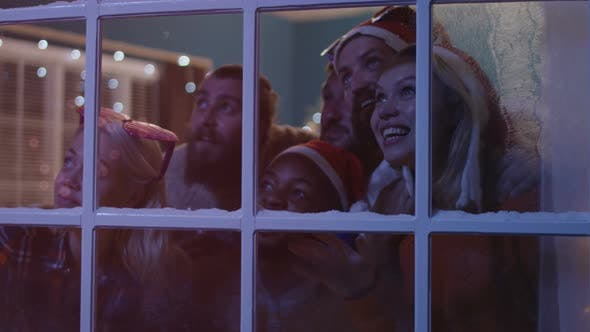 Cover Image for Excited Friends Looking Out in Window During Christmas