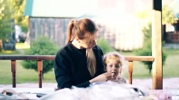 Thumbnail for Young Pretty Mother Is Feeding Her Daughter with Porridge, They Are Sitting in a Summer House