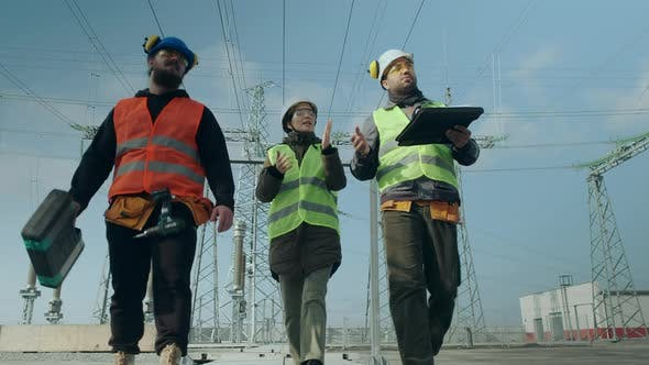 Employees Walk Along Power Substation and Discuss Project