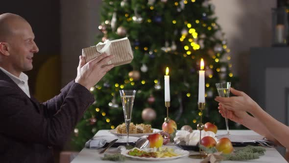 Cover Image for Caucasian Husband Giving Wife Christmas Present in Restaurant