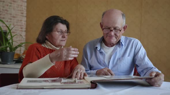 Thumbnail for Pleasant Memories, an Elderly Happy Married Couple Share a Memory Flipping Through an Old Family