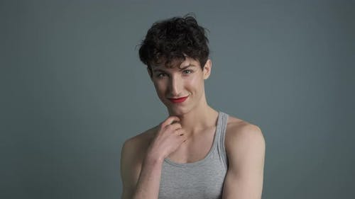 Portrait of Handsome Androgynous Man with Makeup Sending Air Kiss To Camera
