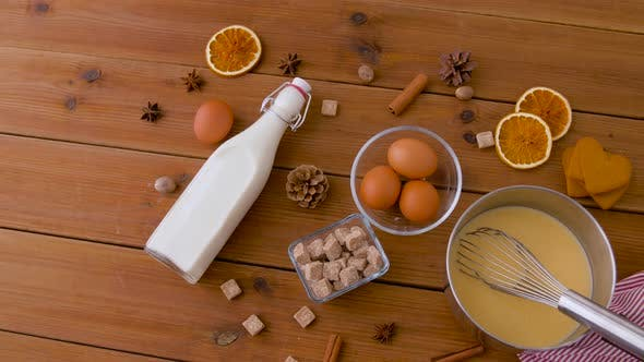 Pot with Eggnog, Ingredients and Spices on Wood