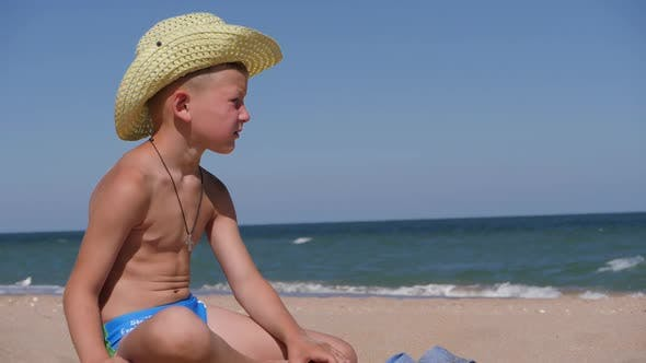 Thumbnail for Boy Sits on the Golden Sand. The Child Wears a Straw Hat with a Large Brim