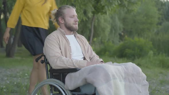 Thumbnail for Portrait of Thoughtful Young Man on Wheelchair Sitting in Park As Cheerful Beautiful Woman Running