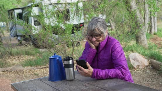 Thumbnail for Active senior woman resting on park bench texting on smart phone in nature.
