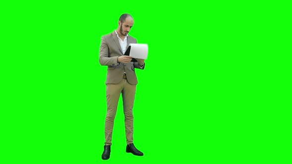 Thumbnail for Concentrated Businessman Reading Important Report on a Green Screen, Chroma Key