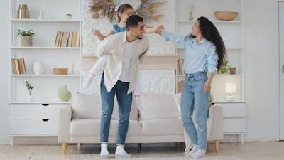 Hispanic Family Dancing at Home Living Room with Little Schoolgirl Daughter Celebrating Enjoying