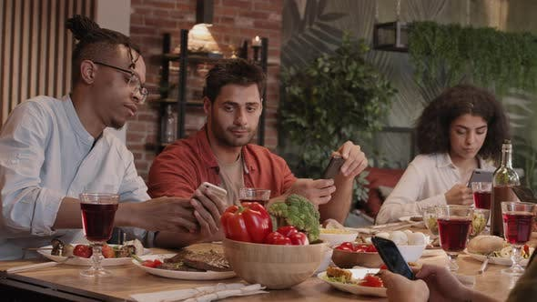 Thumbnail for Multiethnic Friends Using Smartphones during Dinner
