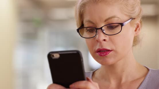 Thumbnail for Close up of successful female wearing glasses texting on smart phone at work