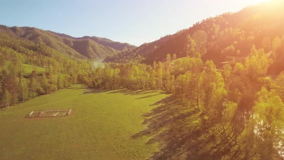 Cover Image for Mid Air Flight Over Fresh Mountain River and Meadow at Sunny Summer Morning. Rural Dirt Road Below.