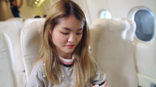 Asian Woman Using Mobile Phone in Airplane