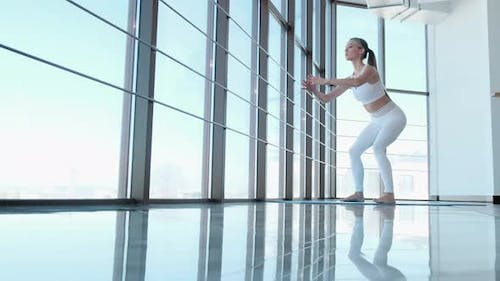 The girl performs exercises to train the legs in the gym on the background of a large window.